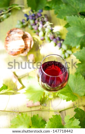 Glass of red wine on a wooden table with leaves of grapes, corkscrew and wine corks and toast and a bunch of young grapes. - stock photo