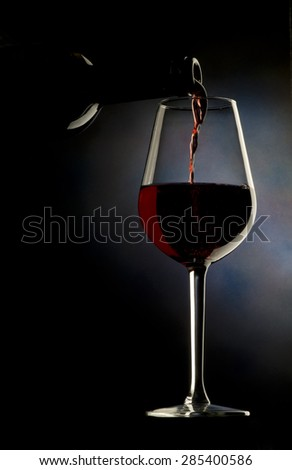 Glass of red wine on dark background - stock photo