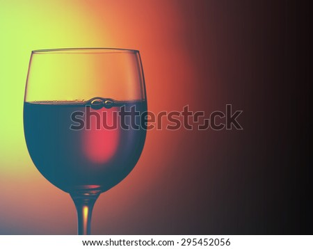 glass of red wine on dark red background.Filtered image: cool cross processed vintage effect. - stock photo