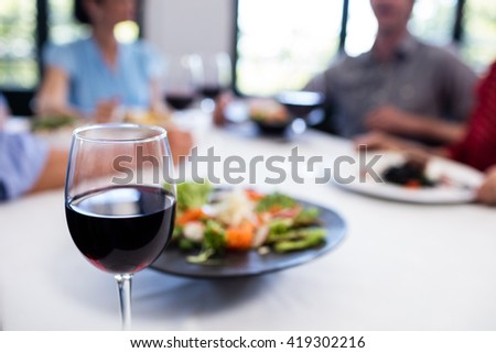 Glass of red wine on the restaurant table and people in background