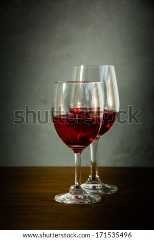 Glass of red wine on wood table with grunge wall background