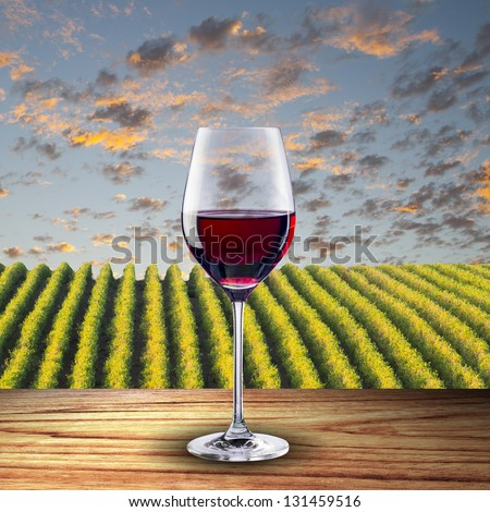 Glass of red wine on wood table with vineyard scene in the background