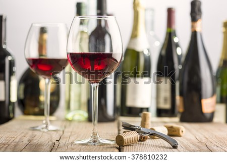 glass of red wine on wooden table near corkscrew and bottle