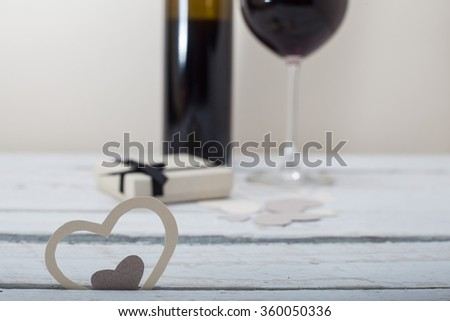 Glass of red wine with a celebration present and fireplace in background - stock photo