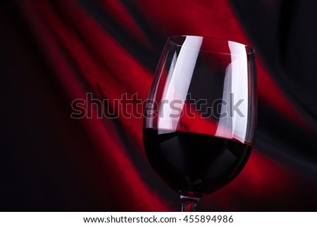 Glass of red wine with a dark background lit by a red light