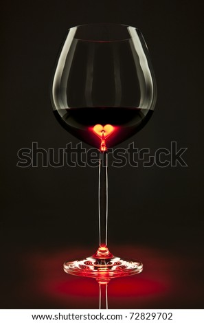 Glass of red wine with a heart inside - stock photo