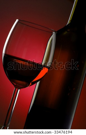 Glass of red wine with bottle beside and an abstract low-light background