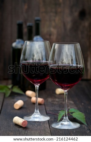 Glass of red wine with corks on old wooden table