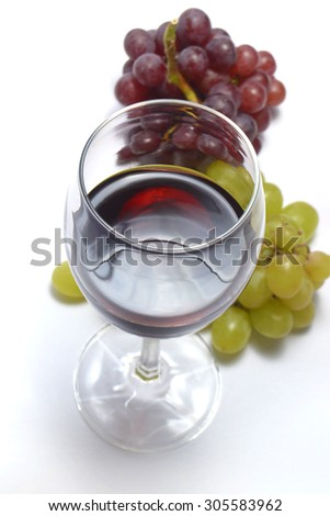 glass of red wine with grape fruits - stock photo