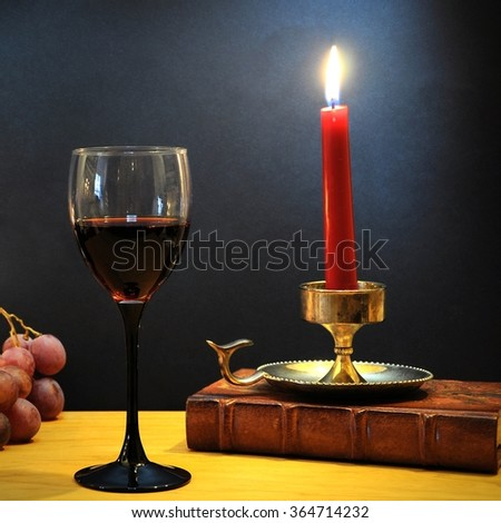 Glass of red wine with grapes, candle and old book - stock photo