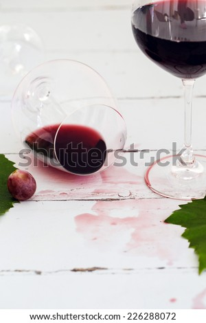 Glass of red wine with grapes on a wooden table - stock photo