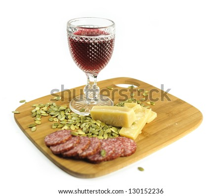Glass of red wine with pumpkin seeds, salami and cheese on the cutting board - stock photo
