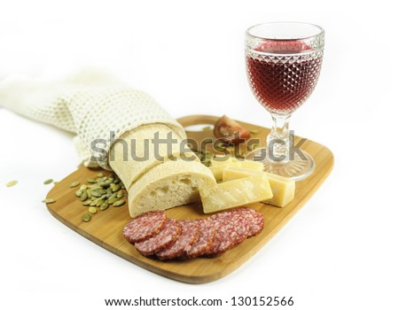 Glass of red wine with pumpkin seeds, salami, tomatoes, bread, pieces of cheese  on the cutting board - stock photo