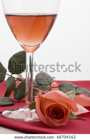 glass of red wine with red table cloth and pink rose on on white background.