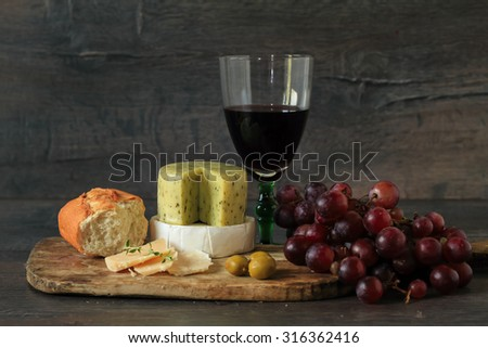 Glass of red wine with various types of cheese, fruits and appetizers - stock photo