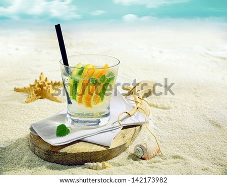 Glass of refreshing chilled gin or vodka cocktail with slices of lemon, lime and orange on a tropical beach with a shell and starfish on golden sand - stock photo