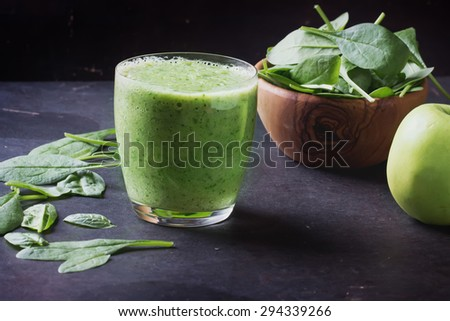 Glass of refreshing green smoothie served with green apple, baby spinach leaves, soya sprouts and an egg yolk - stock photo