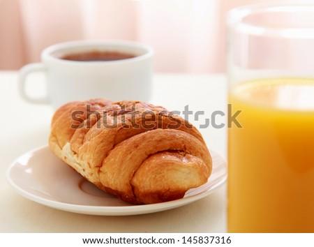 Glass of refreshing orange fruit juice and croissant - stock photo