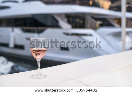 Glass of rose wine and a yacht on the background