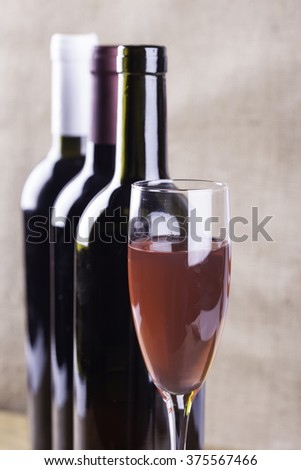 glass of rose wine on the background bottles - stock photo