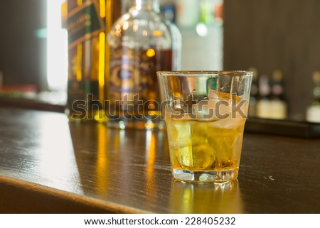 Glass of scotch or whiskey on the rocks standing on a counter in a pub or bar with glassware in the background - stock photo