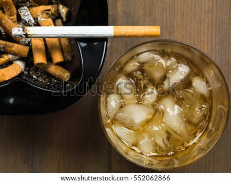 Glass of Scotch Whiskey on the Rocks and a Cigarette Burning in an Ashtray