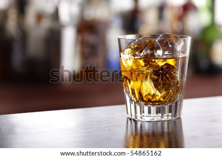 Glass of scotch whiskey shot in bar with room for copy - stock photo