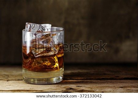 glass of scotch whiskey with ice cubes on a rustic wooden table, copy space in the brown background - stock photo