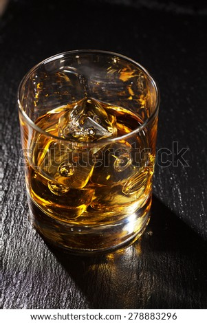 Glass of scotch whiskey with ice on black stone table - stock photo