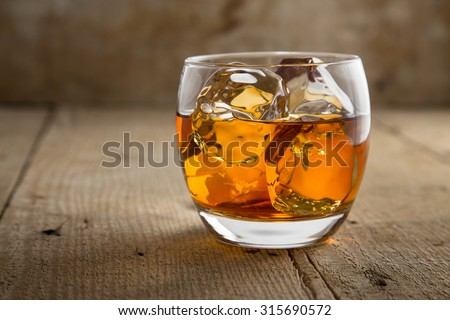 Glass of scotch whisky brandy with ice on wooden bar table rustic barrel surface  - stock photo