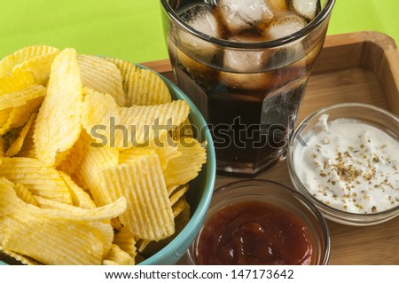 glass of soda potato crisps and ketchup and mayonnaise on bamboo tray - stock photo