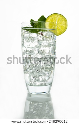 Glass of sparkling  water with ice cubes garnished with a slice of lime and mint on white background - stock photo