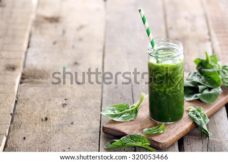 Glass of spinach juice on wooden background - stock photo