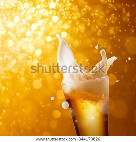 glass of splashing beer against golden bokeh background - stock photo