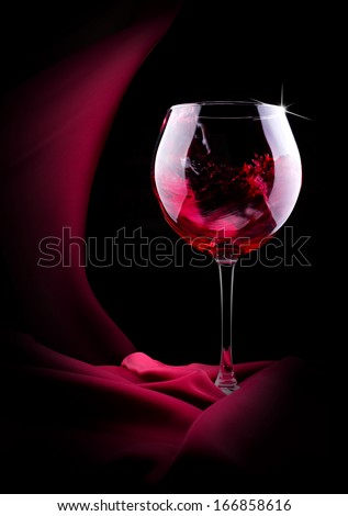 glass of splashing wine with red silk on black background - stock photo
