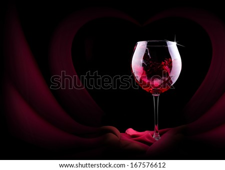 glass of splashing wine with red silk on black background
