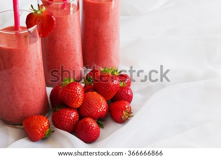 glass of strawberry smoothie and ripe strawberries on the table. health and diet concept. selective focus - stock photo