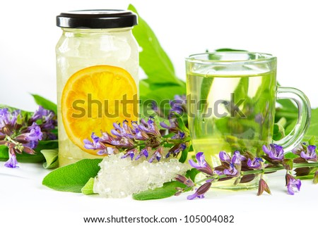 Glass of sweet herbal tea with flowering salvia , sugar crystals and sliced orange, a medicinal remedy used in Auyurveda naturopathy - stock photo
