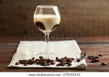 Glass of tasty panna cotta dessert on plate, on wooden table - stock photo