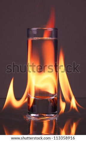 Glass of tequila and flames - stock photo