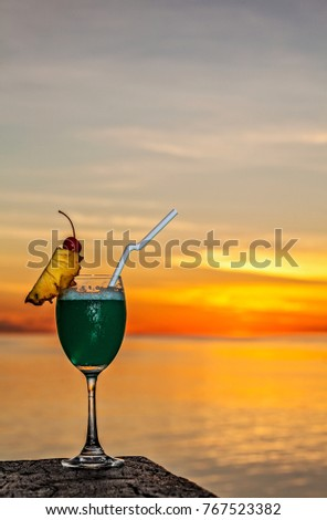 Glass of the soft drink is on a beach table (Maldives, The Indian Ocean)