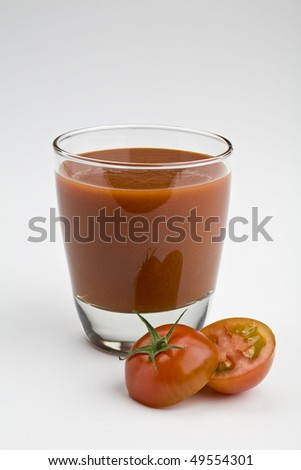 Glass of tomato juice on white with sliced tomato - stock photo