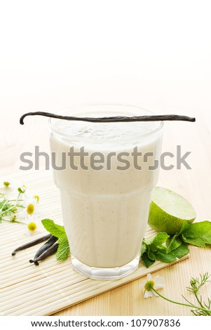 Glass of vanilla milkshake with vanilla beans, limes, mint leaves and daisy flowers on wood - stock photo
