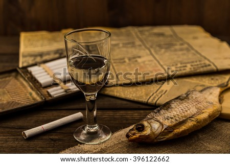 Glass of vodka with a cigarettes and newspaper with canvas on an old wooden table. Angle view, shallow depth of field