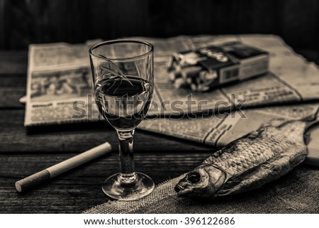 Glass of vodka with a cigarettes and newspaper with canvas on an old wooden table. Angle view, shallow depth of field, image in black and white tones - stock photo
