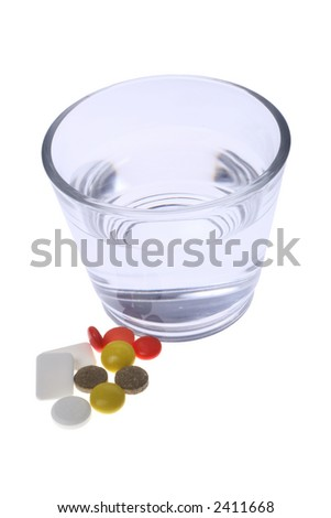 glass of water and dose of pills - stock photo