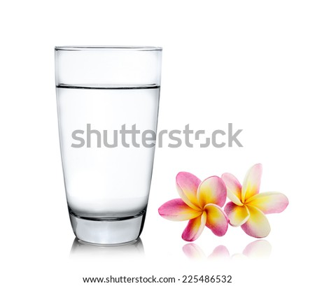 Glass of water and frangipani flower isolated white background - stock photo