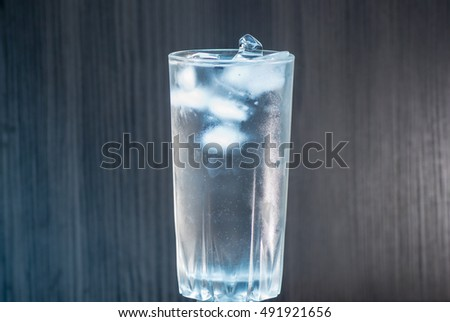 glass of water and ice on wooden background with backlight