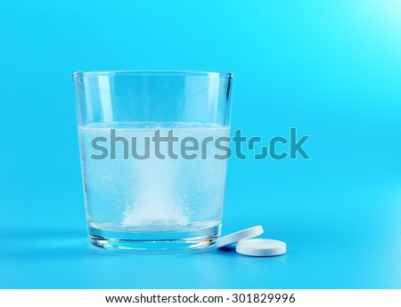 Glass of water and pills on blue background - stock photo