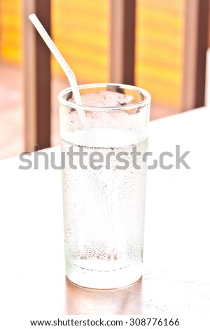 Glass of water and straw on a wooden table.